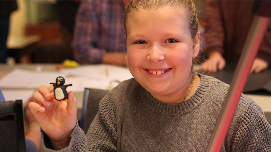 A girl smiles holding up a claymation sculpture of a miniature penguin she created