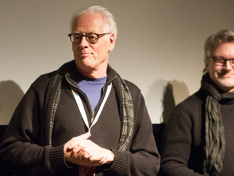 Two men are standing in front of a screen at a film festival