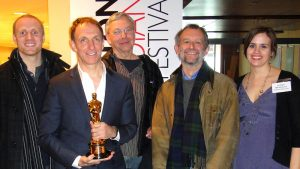 A group of people pose with a man who is holding an Oscar statuette