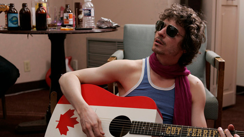A man playing a guitar with a Canadian flag on it from the film Guy Terrifico