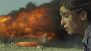 A woman in shock stands with blood on her face with huge flames and smoke in the background