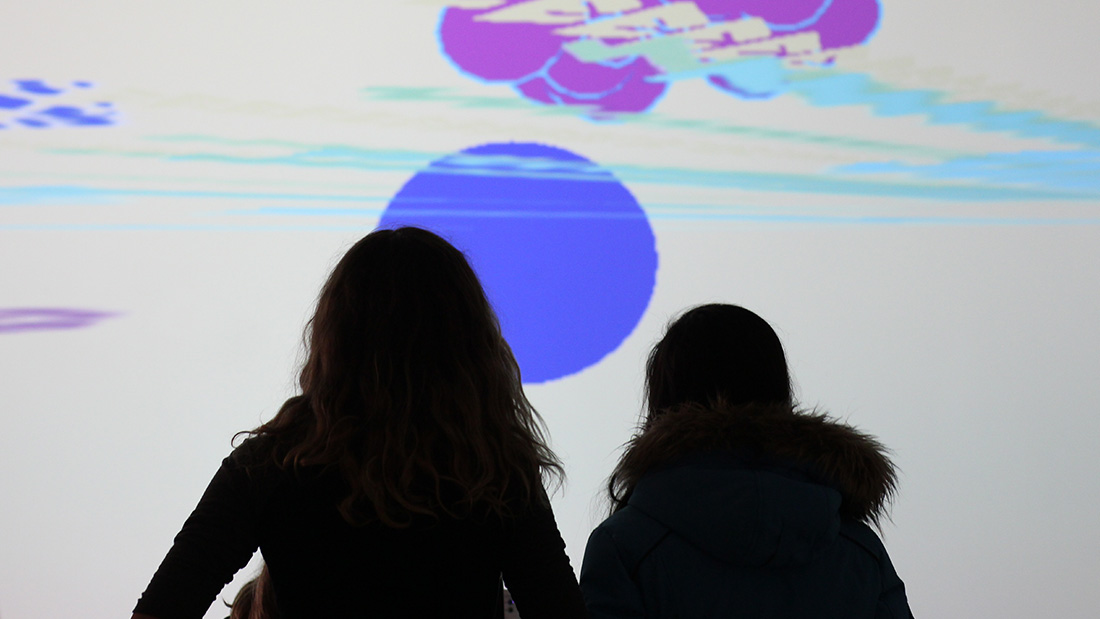 2 girls play a video game projected on a gallery wall