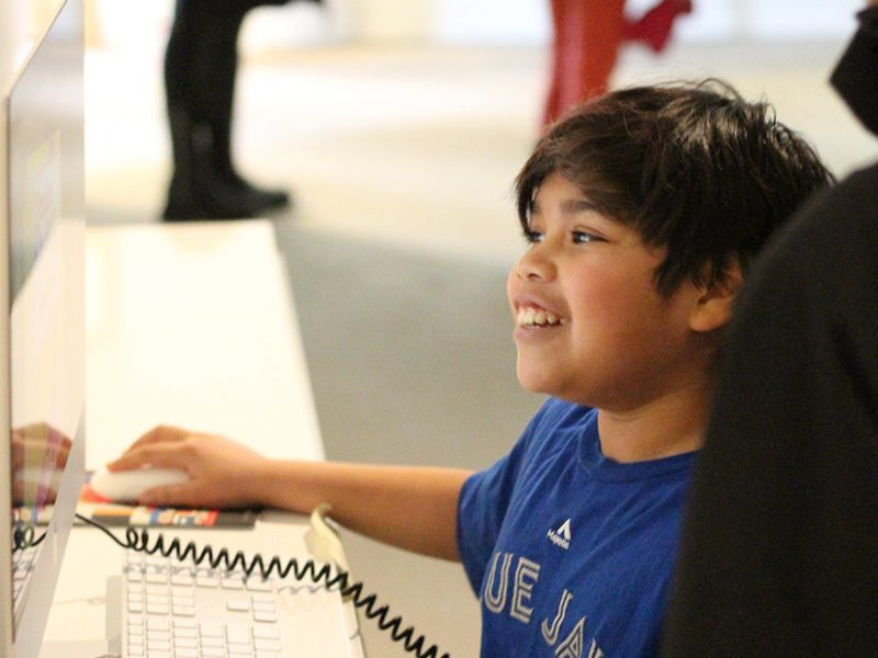 A child plays a video game on a computer in a gallery