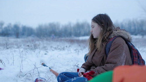 A young girl sits in the snow in a desolate field in the country