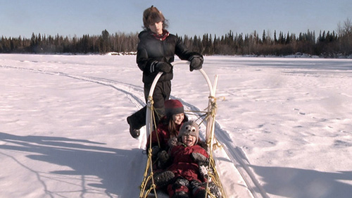 A mother stands on the back of a dog sled with two happy children in the sled