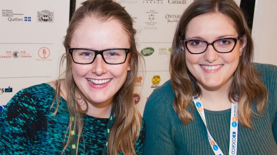 Two women both wearing glasses smile for the camera
